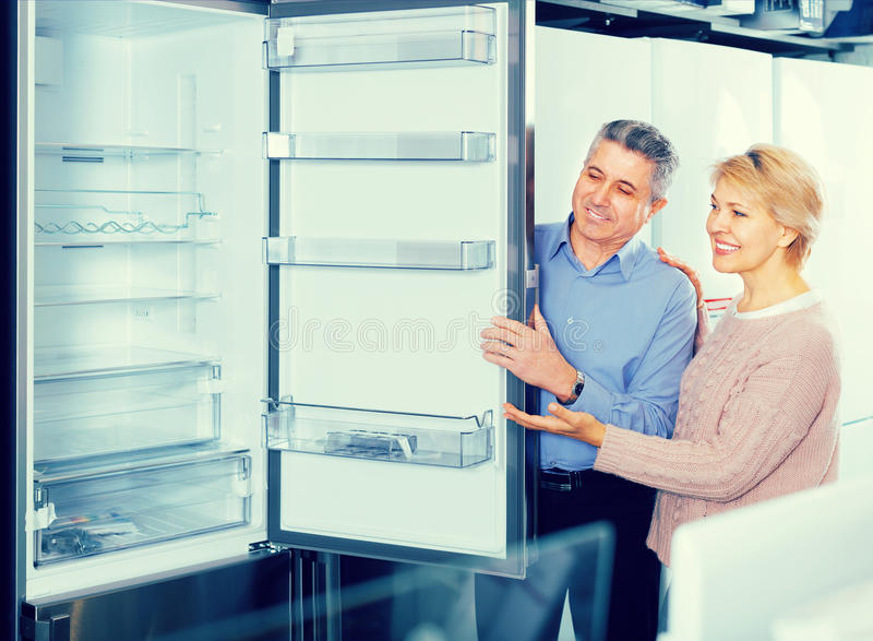 Couple chooses ice-box in shop of household appliances royalty free stock images