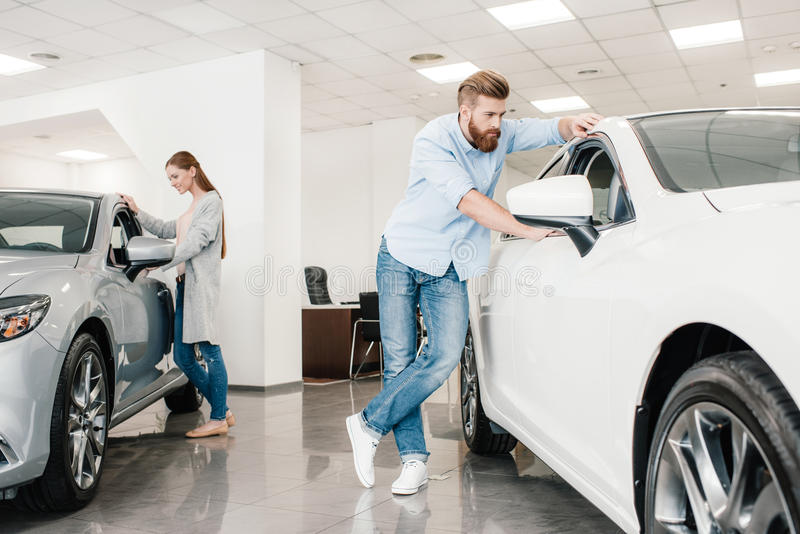 Couple choosing car, man and woman looking on various cars royalty free stock images
