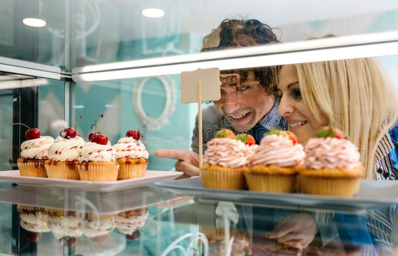 Couple choosing a cupcake stock image