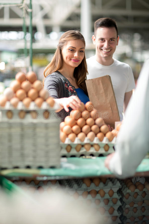 Couple choosing eggs at the market royalty free stock photos