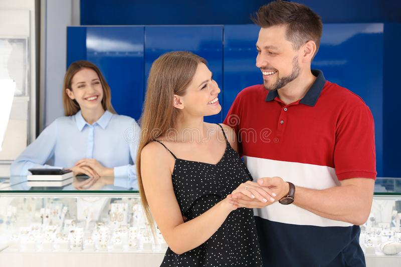 Couple choosing engagement ring in jewelry stock photo