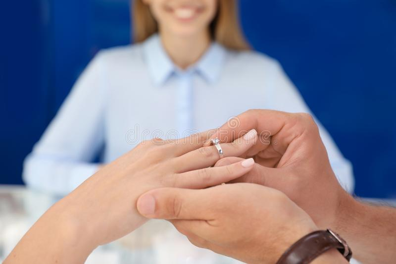 Couple choosing engagement ring in jewelry store, royalty free stock photo