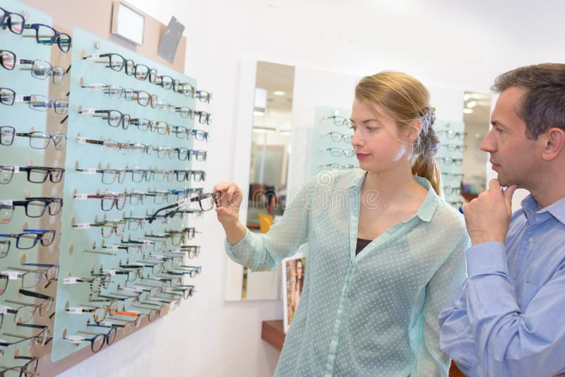 Couple choosing glasses in opticians. Couple royalty free stock photography