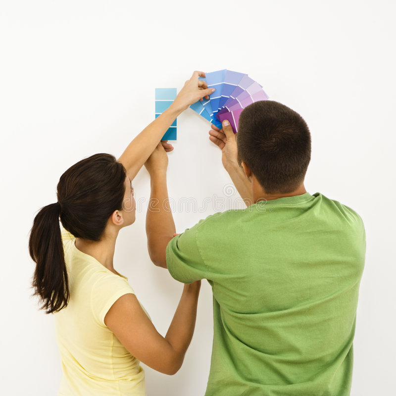 Couple choosing home color. Attractive young adult couple holding color paint samples up to white wall royalty free stock photos