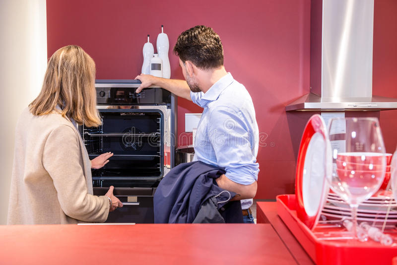 Couple Choosing Microwave In Hypermarket royalty free stock photos