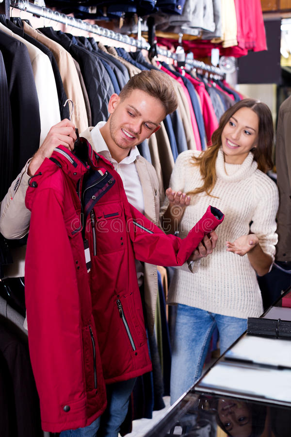 Download Couple Choosing New Coat In Men's Cloths Store Stock Photo - Image: 83702132