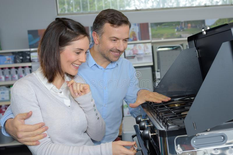 Couple choosing new gas-stove in appliances store. Couple stock image