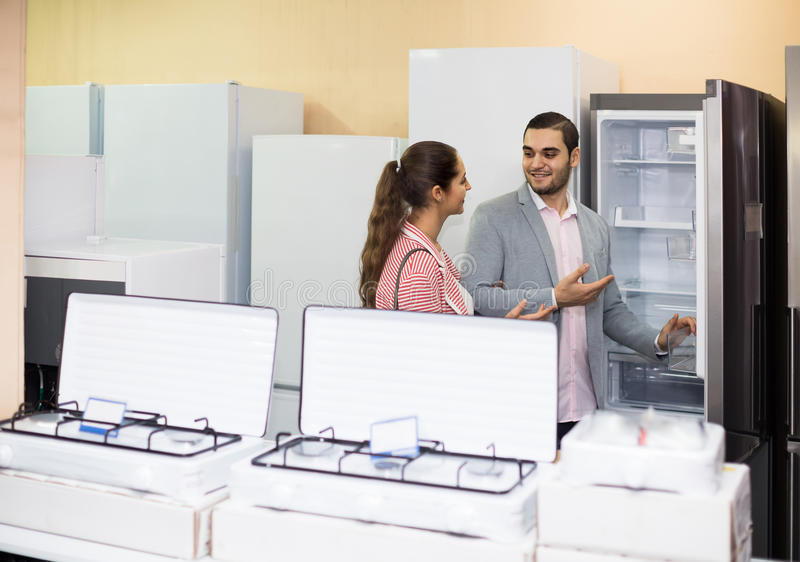 Couple choosing new refrigerator in hypermarket. Happy russian couple choosing new refrigerator in hypermarket and smiling stock photography