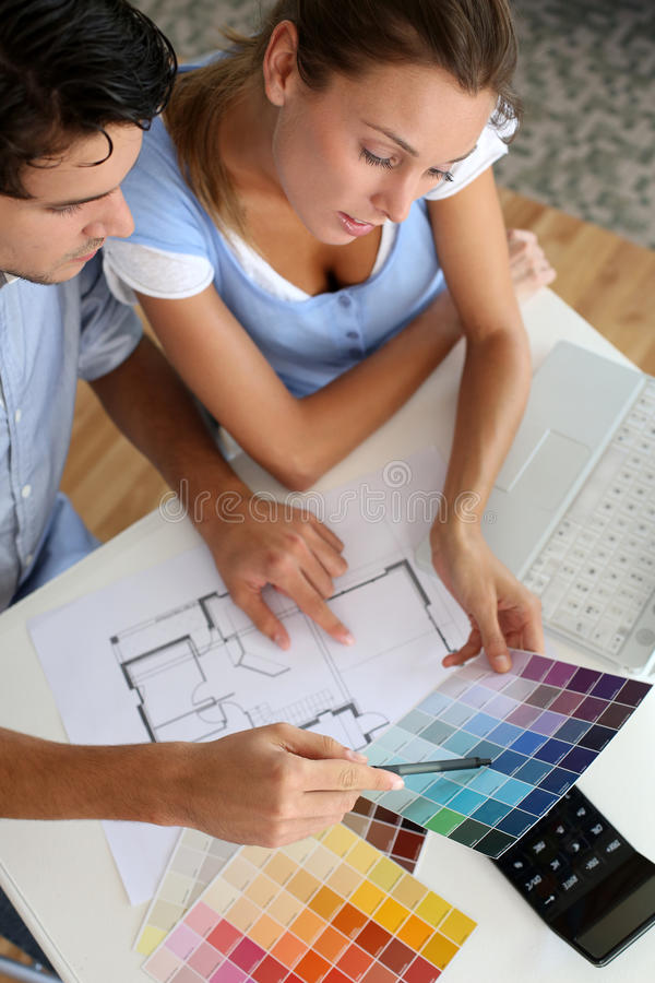 Couple choosing paint colours royalty free stock photography