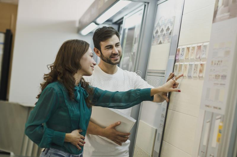 Couple choosing tiles in ceramic and furniture shop for new home stock images