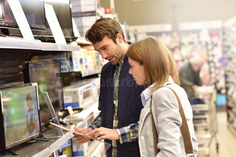 Couple choosing a tv set in supermarket stock photo