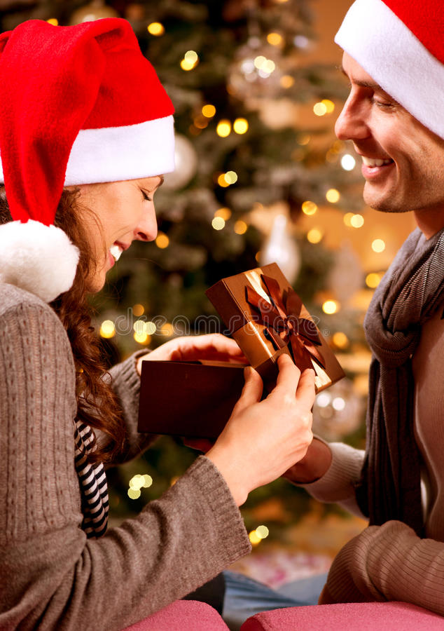 Couple with Christmas Gift at Home royalty free stock images
