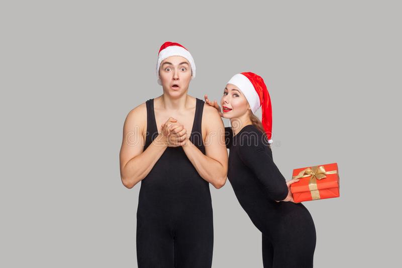 Couple in christmas hat. Shocked man looking at camera. woman ho stock photos