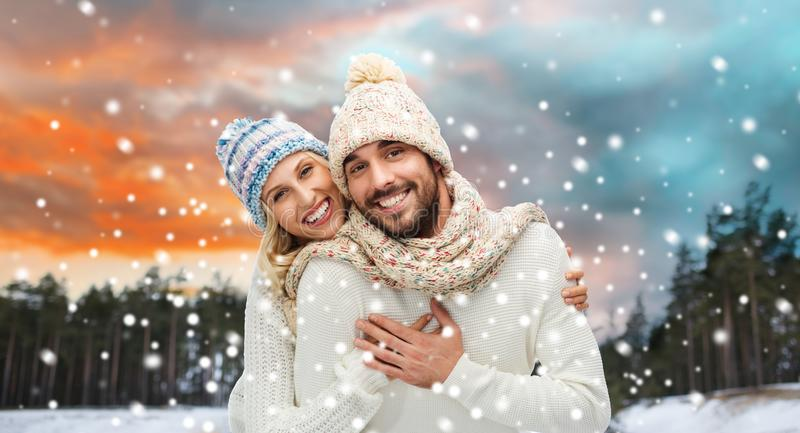 Smiling couple in winter clothes hugging stock photo