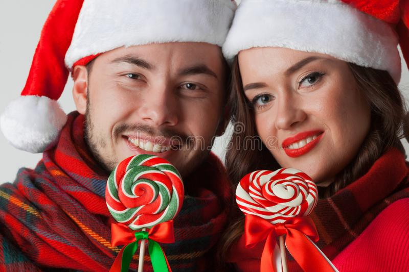Couple in christmas santa hats with lollipops. Young happy smiling couple in christmas santa hats with lollipops stock photography