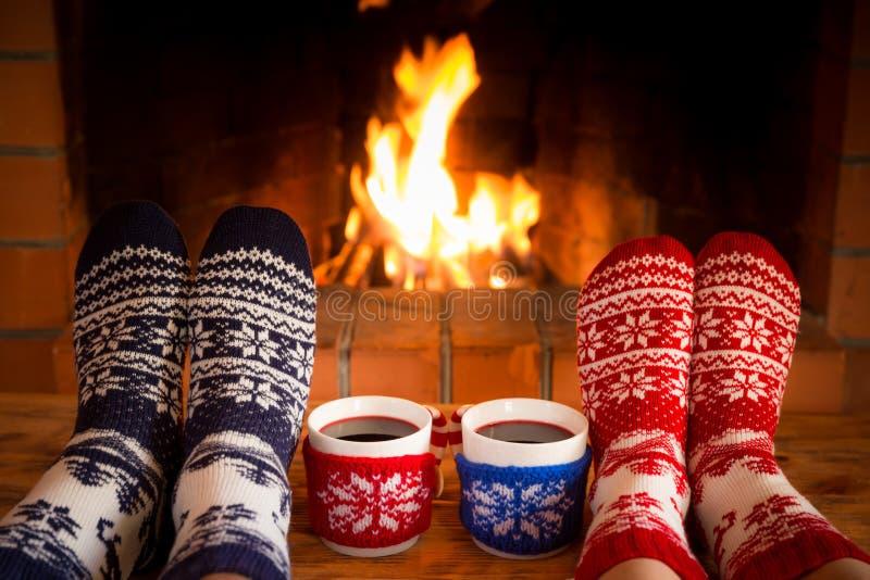Couple in Christmas socks near fireplace stock image