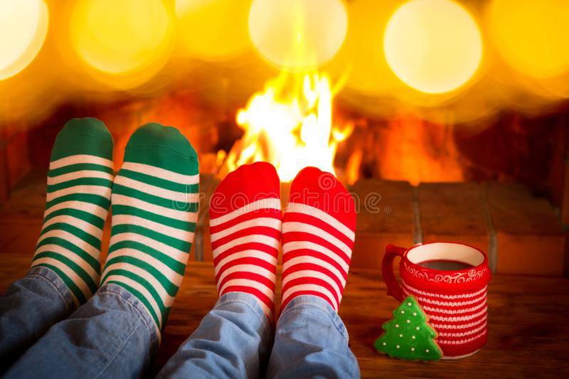 Couple in Christmas socks near fireplace stock images