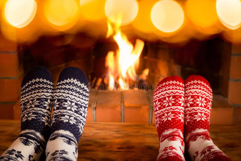 Couple in Christmas socks near fireplace stock photo