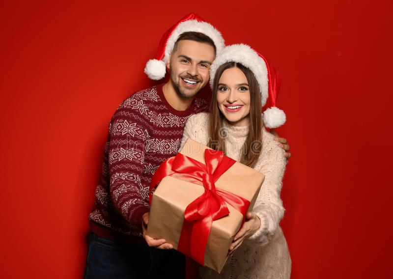 Couple in Christmas sweaters and Santa hats with gift box. On red background stock images