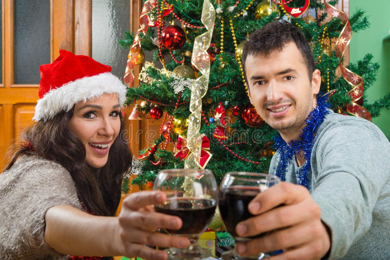 Couple at Christmas time making toast with glasses of wine royalty free stock photography