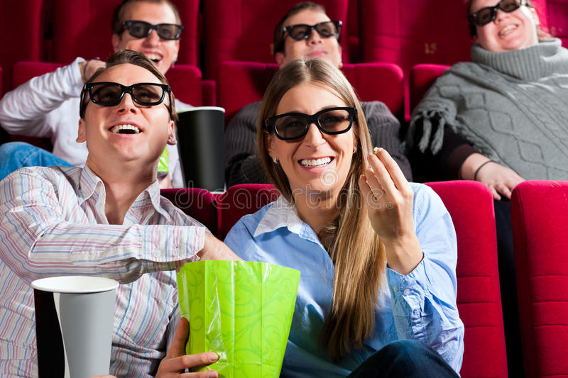 Couple in cinema with 3d glasses. Couple in cinema theater watching a movie in 3D with glasses and popcorn royalty free stock image