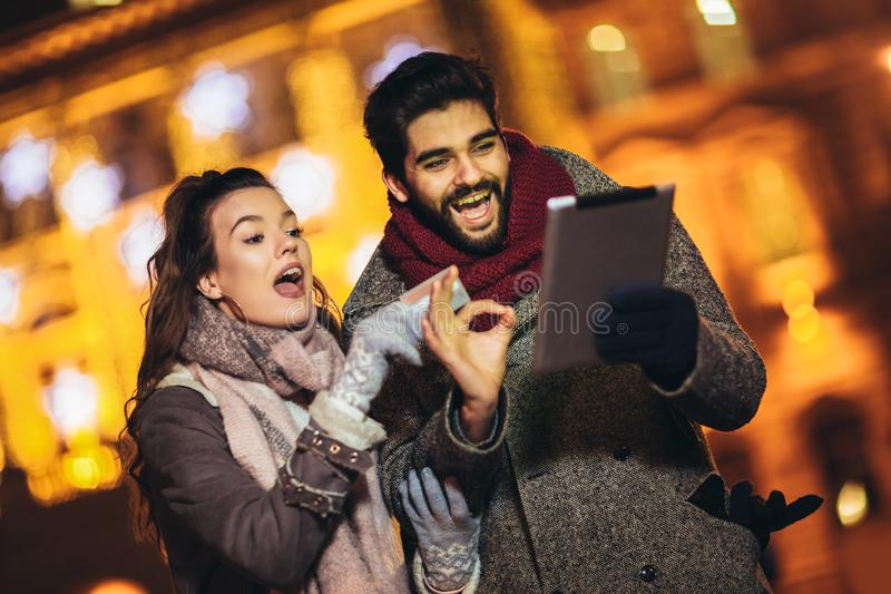 Couple in the city centre with holiday`s brights in background. Couple browsing digital tablet. They are using credit card stock photos