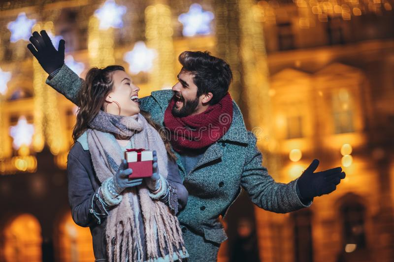 Couple in the city centre with holiday`s brights in background. Man presenting gift to woman royalty free stock photos