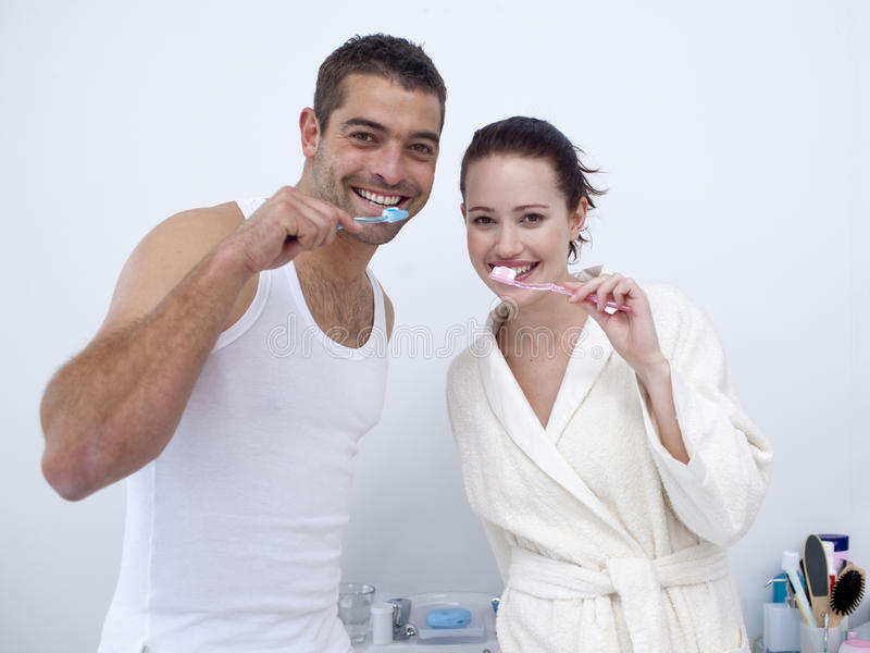 Couple cleaning their teeth in bathroom