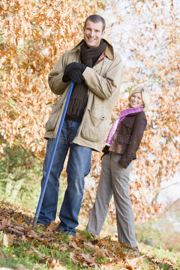 Download Couple Clearing Autumn Leaves Stock Photo - Image: 5306934