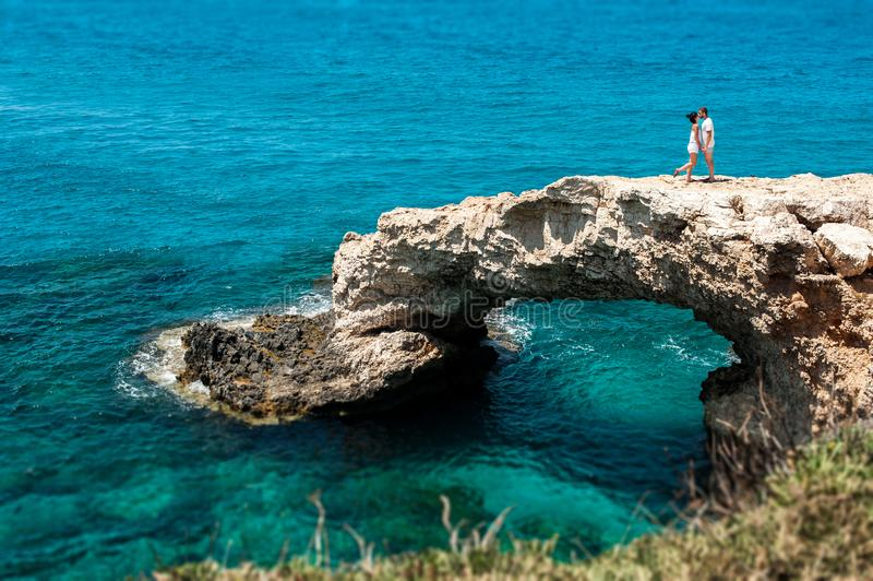 The couple on the cliff by the sea. Honeymoon lovers. Man and woman traveling. Couple in love on vacation. Newly married couple. Sea tour. Honeymoon trip. Man stock images