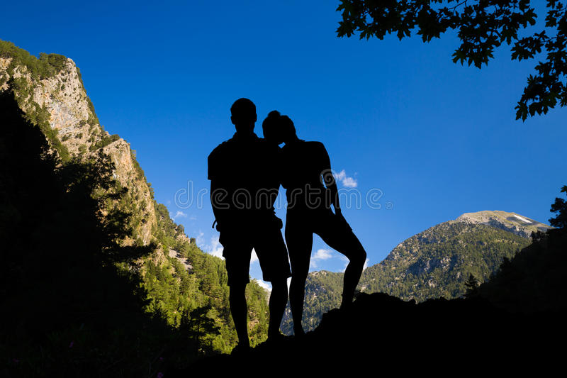 Couple climbers or hikers celebrating inspirational landscape. Happy couple tourists looking at mountains view, family silhouette. Hikers traveling in beautiful stock photography