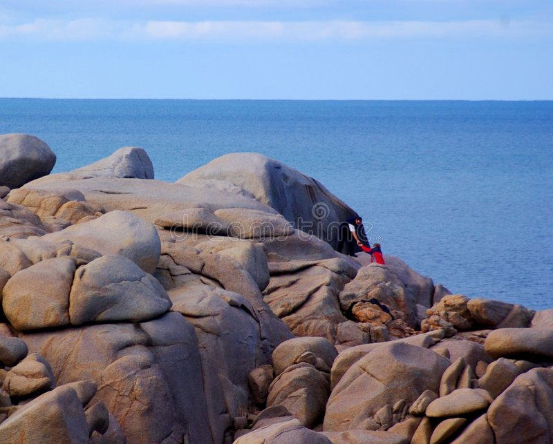 Couple climbing rocks by sea stock images