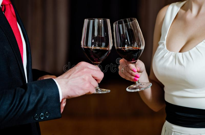 Couple clink glasses with red wine at meeting or wedding stock photo