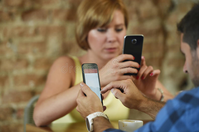 Couple at coffee shop with man and woman using mobile phone networking ignoring each other royalty free stock image