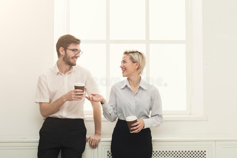 Couple of colleagues drinking coffee near window stock photography