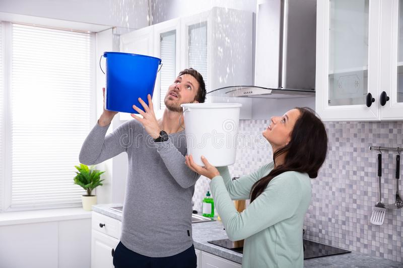 Couple Collecting Water Leaking From Ceiling In Bucket. Close-up Of A Worried Young Couple Collecting Water Leaking From Ceiling In The Blue Bucket stock images