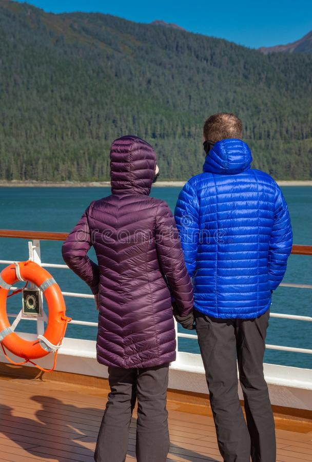 Couple in colorful purple and blue winter puffer jackets view Alaska, USA coastl from ship`s deck on a sunny cold day. Traveling couple in colorful winter stock photos