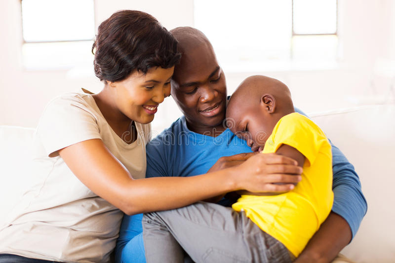 Couple comforting ill son. Loving young african couple comforting their ill son at home stock photography