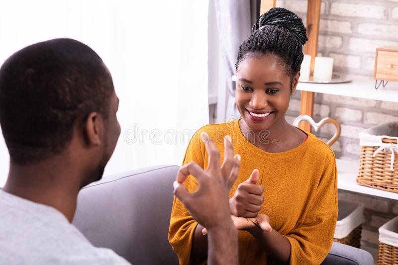 Couple Communicating With Sign Languages royalty free stock image