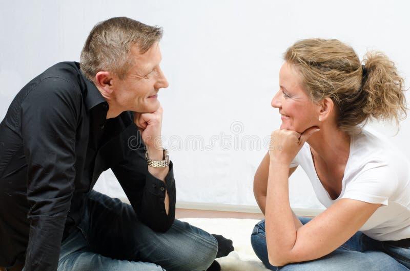 Couple communicating -sitting on the floor royalty free stock photo
