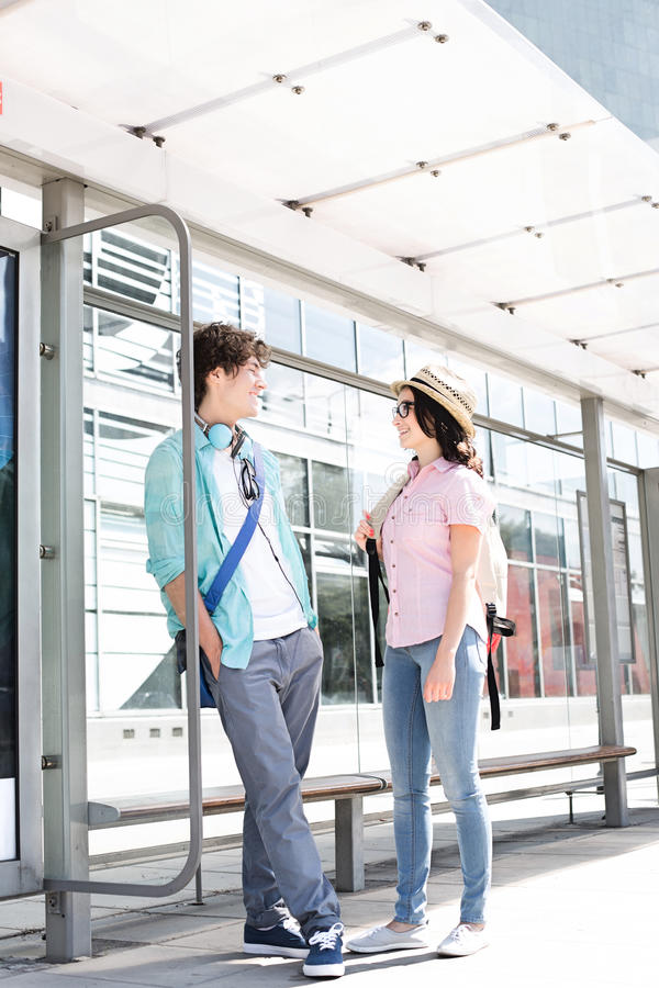Couple communicating while waiting at bus stop stock photos