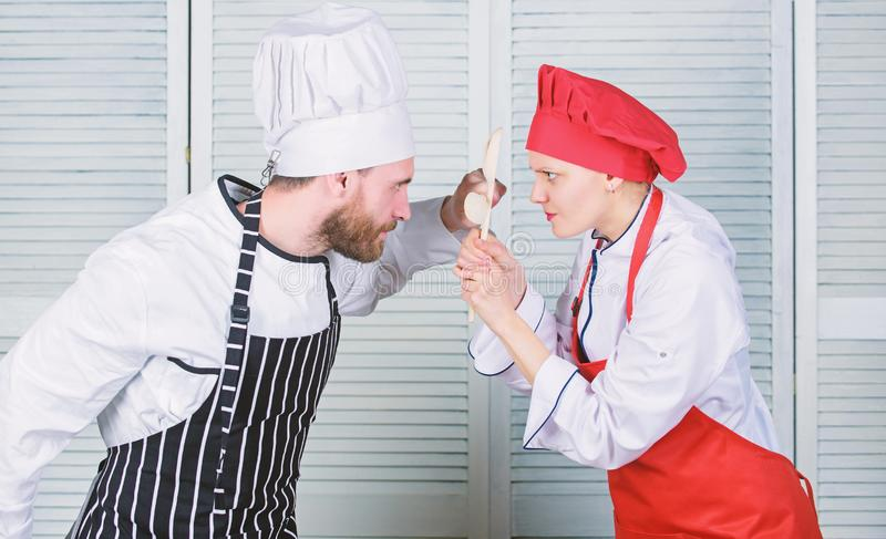 Couple compete in culinary arts. Who cook better. Culinary battle concept. Woman and bearded man culinary show. Couple compete in culinary arts. Who cook better stock photo