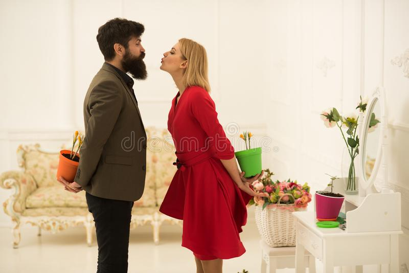 Couple concept. Couple in love celebrate spring. Couple of man and woman hide flowers behind their backs. Couple romance royalty free stock photos