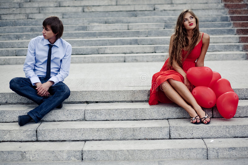 Couple in conflict. Romantic teenager couple in quarrel sitting on staircase