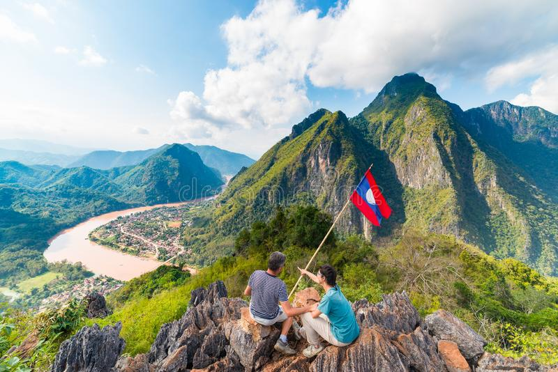 Couple conquering mountain top at Nong Khiaw panoramic view over Nam Ou River valley Laos national flag scenic mountain landscape. Famous travel destination in stock photos