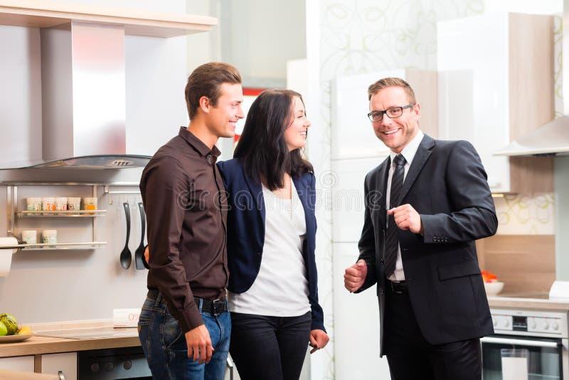 Couple consult salesman for domestic kitchen. Man and women consult salesman for domestic kitchen in studio or furniture store stock photo