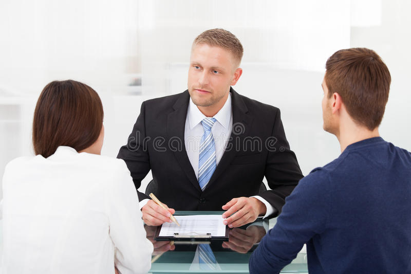 Couple consulting financial advisor. Rear view of young couple consulting financial advisor at office desk royalty free stock images