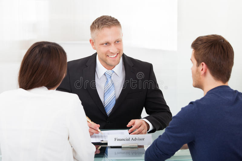 Couple consulting financial advisor. Rear view of young couple consulting financial advisor at office desk royalty free stock photography
