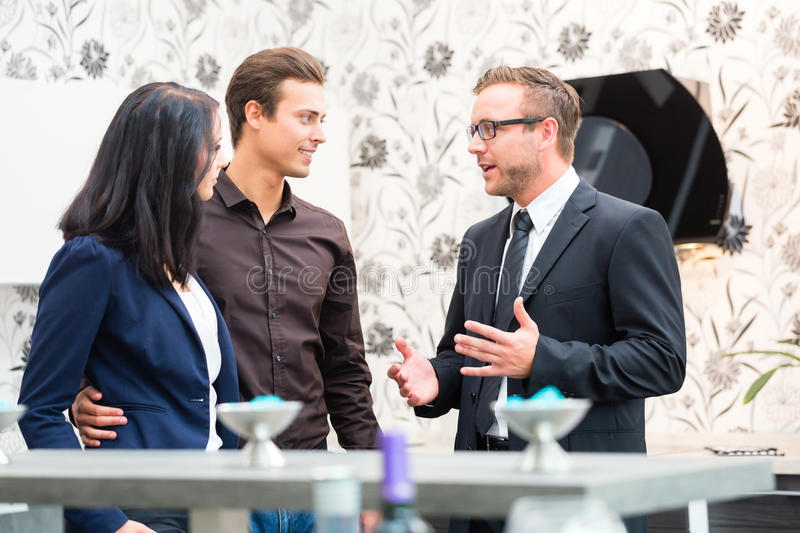 Couple consulting salesman for domestic kitchen. Man and women consulting salesman for domestic kitchen in studio or furniture store stock photos
