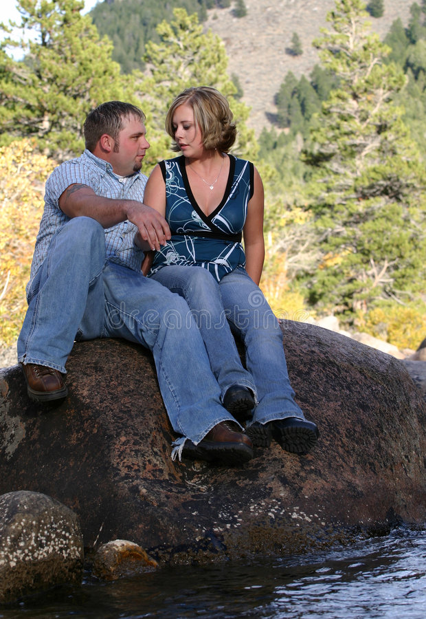 Couple Conversation. Young rural couple in the great outdoors having an intimate conversation. They are sitting on a boulder in the river during the Fall season stock images